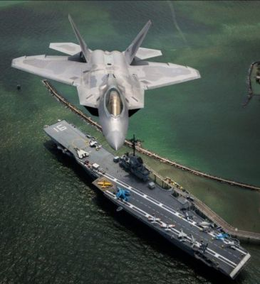 An F-22 Raptor soars over an old aircraft carrier.