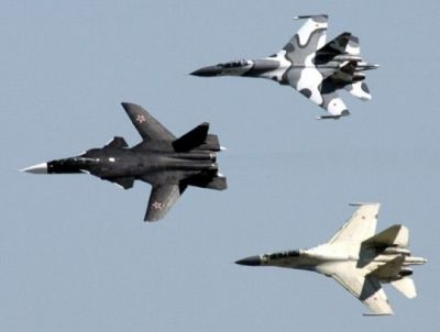 A formation flight of a Russian Sukhoi Su-47 and Su-27 fighter jets.