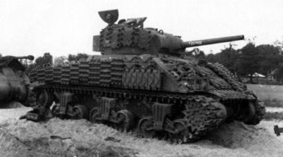 An M4 Sherman absolutely covered in extra track links, likely intended to serve as additional armor for the crew in the days after D-Day.
