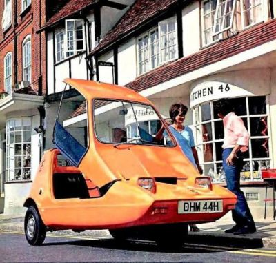 """A promotional photo for the 1970 Bond Bug, a three-wheel """"city"""" car intended for urban commuters. Despite being something of a cross between a tent (it had canvas doors) and a motorcyle (on account of the steering), it was still able to reach a (terrifying!) 75 miles per hour."""