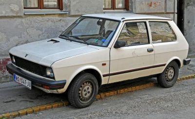 A Yugo waits on a curb in Slovenia.