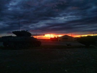 A Sherman tank on display at dawn.